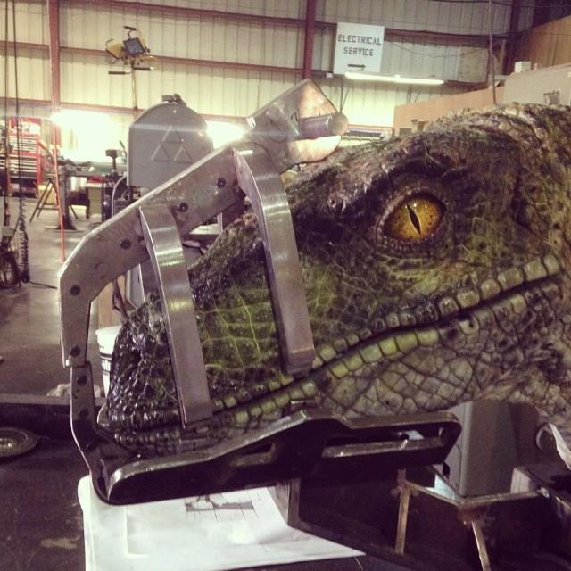 Set photo showing muzzled velociraptor in JW