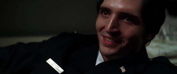 Shift Thomas wearing Rachel Dawes' name; signaling her as Joker's next victim.